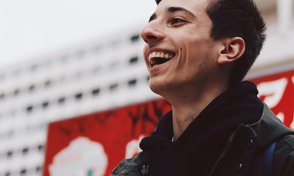 jongen voor gebouw lacht kijkt opzij