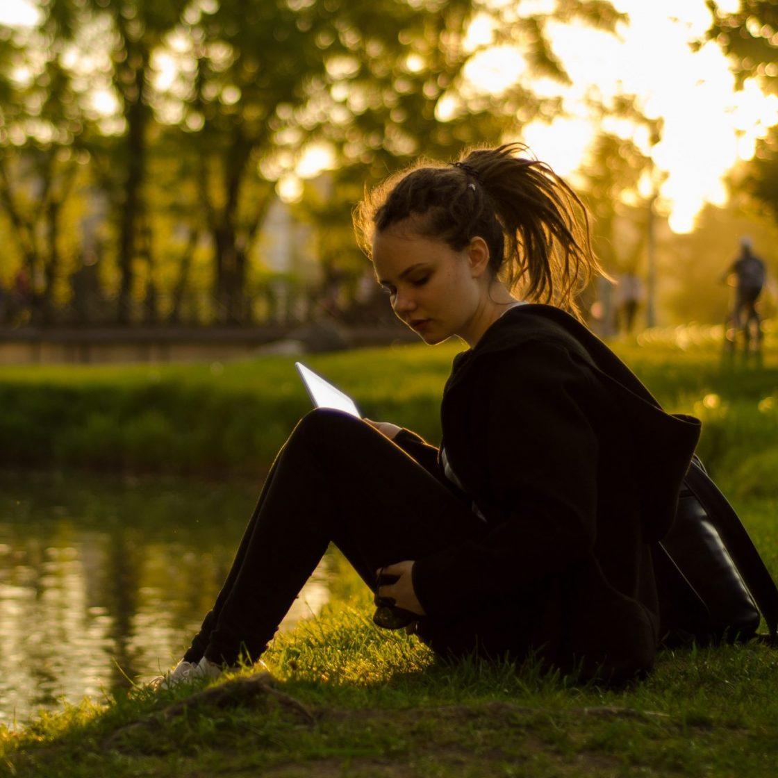 meisje studeert in een park in het gras